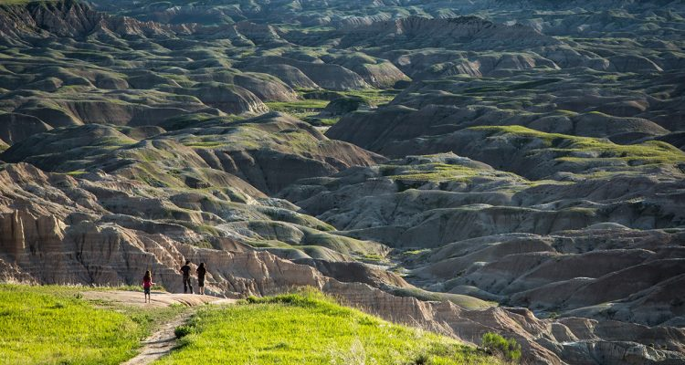 Oglala Lakota children standing at the Red Shirt Table overlook surveying Badlands National Park