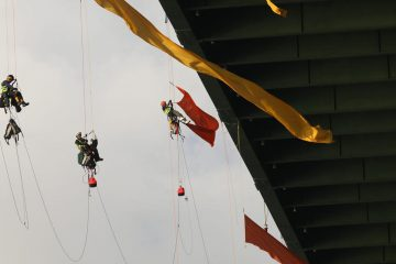 Greenpeace activists hang from a bridge in Houston