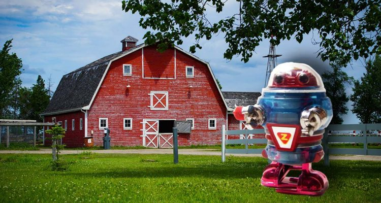 toy robot stands in front of white farm fence and red barn